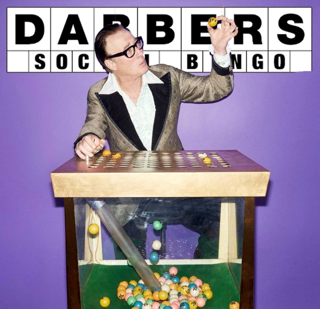 Peter Perke - bingo caller : man dressed in vintage clothing and wearing glasses sitting behind a blower bingo machine holding a ball up in the air