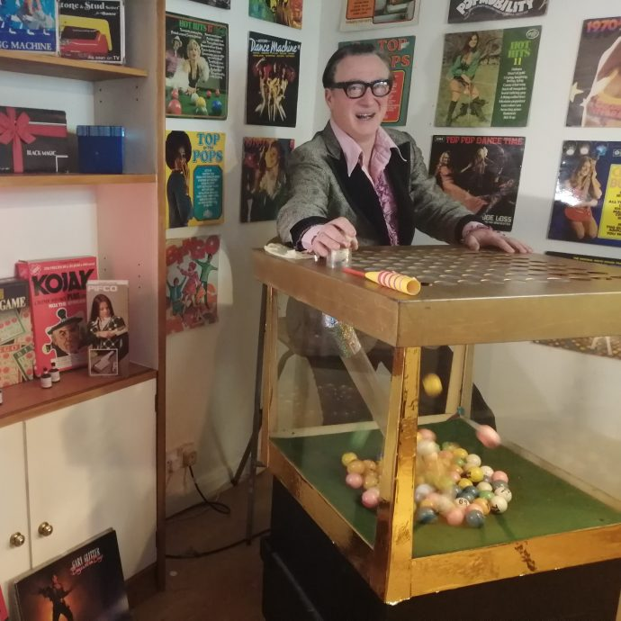 Comedy Bingo Host Peter Perky sitting by his retro 1970s blower bingo machine
