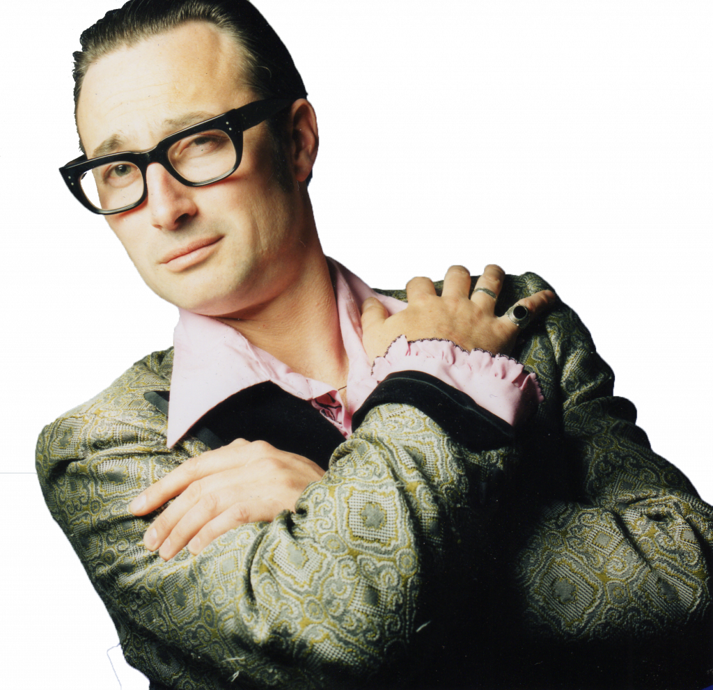 Man wearing glasses and retro vintage clothing looking at camera with his arms crossed over his chest